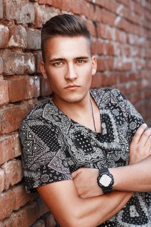 レンガ壁の背景にアメリカからハンサムな若い男が立っています。 写真素材
