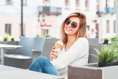 ファッショナブルな美しい笑顔の女性にラウンド サングラスとアイスクリームは夏のカフェでリラックスします。 写真素材