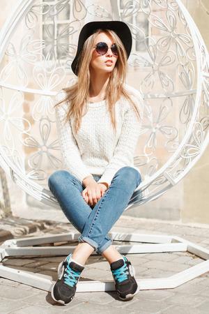 白い浮遊椅子に座って美しいファッショナブルな女の子。 写真素材