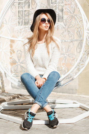 Beautiful fashionable girl sitting in a white suspended chair.