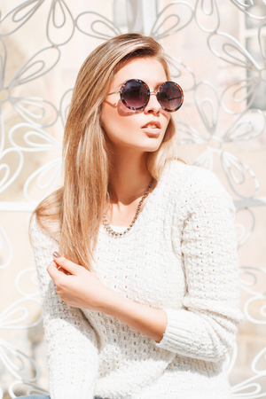 Outdoor fashion portrait of young pretty woman with round sunglasses in summer sunny day on street. Stockfoto
