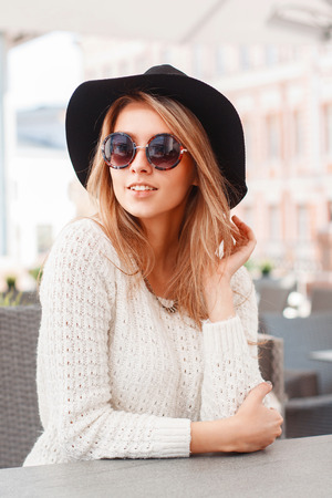 Portrait of a young pretty woman in a black hat and round sunglasses. Beautiful girl sits in summer cafe.