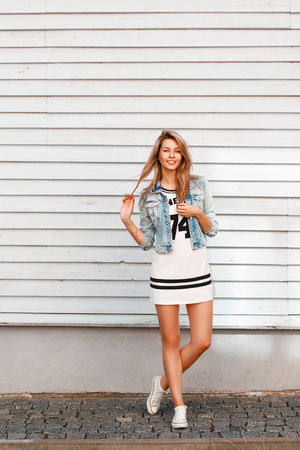 Cheerful beautiful woman with a smile in a denim jacket standing near a white wooden wall.