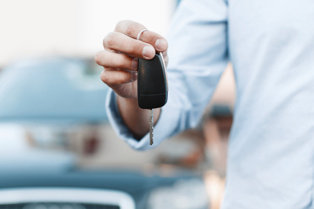 Businessman holding a car key.