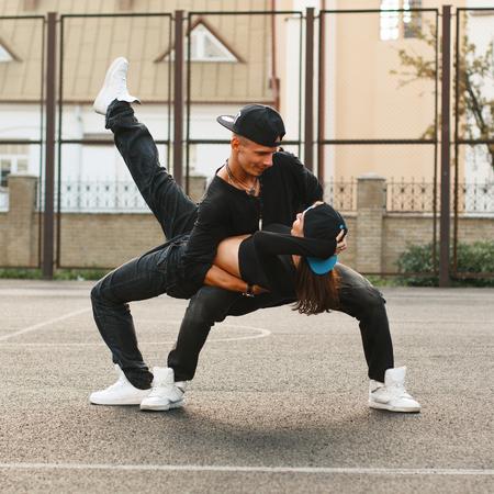 pareja bailando: Hermosa joven pareja bailando hip-hop en el estadio. El tipo con la chica en sus brazos.
