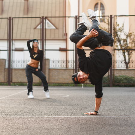 The young dancer standing on his hand. Dancing hip hop with a beautiful girl. Standard-Bild