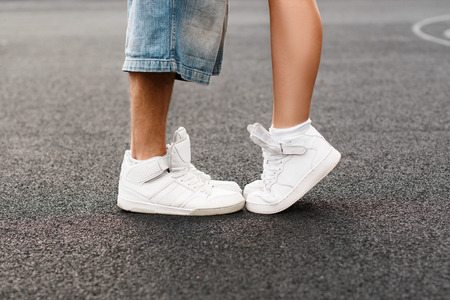 trotters: Young hip-hop couple kissing in asphalt. Kiss love standing. Stock Photo
