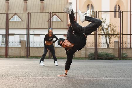 danseuse: Beau mec dans un habit noir de danse hip-hop �l�gant. danseur debout sur sa main. La jeune fille est derri�re le gars.