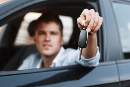 llaves: Hombre de negocios sentado en un coche y dar una llave del coche.