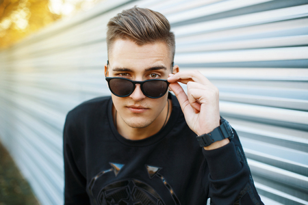 Young handsome man in stylish black clothes looking through sunglasses.