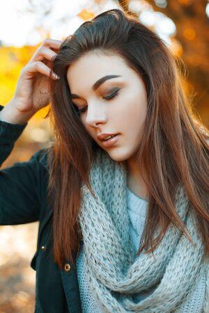 carita feliz: Primer plano retrato de una hermosa joven en el su�ter de punto, bufanda y una chaqueta negro en el parque del oto�o