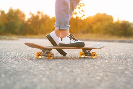 jeune fille: Fille debout sur une planche � roulettes. Gros plan des pieds et de planche � roulettes.