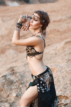 belly dance: Fashion Beauty and stylish girl. Spirituality dance. Pretty Sexy Woman With Luxury glossy gold eastern Makeup danceing tribal fusion. Indian accessories (oriental jewelry)