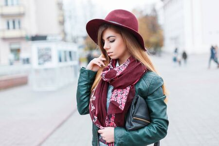 bustle: Beautiful girl in a hat, scarf and jacket on the background of the city bustle Stock Photo