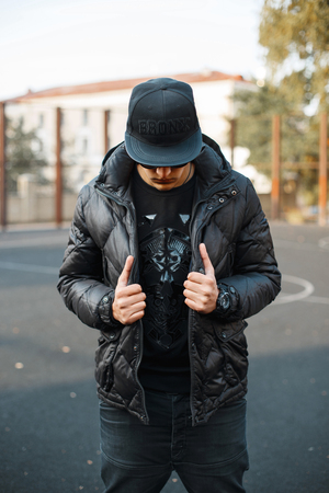 Young trendy guy dressed in black cap and a black jacket on the street