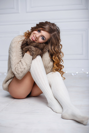 gaiters: Pretty woman in winter mittens sitting on the floor