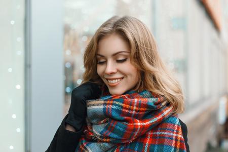 ヴィンテージのスカーフとお店のウィンドウの背景に黒いコートで笑顔で美しい少女