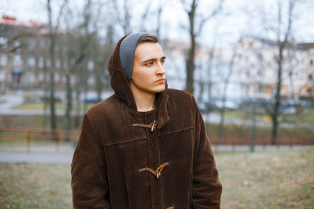 knit cap: Young stylish guy in an old jacket and knit cap on a background of the autumn park