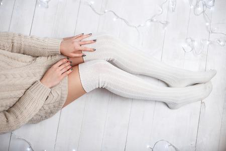 Beautiful female legs in white knitted socks on a white wooden floor