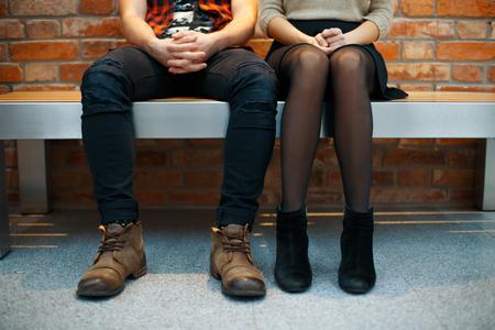 おしゃれなスタイリッシュなカップルがベンチに座っています。足のクローズ アップ