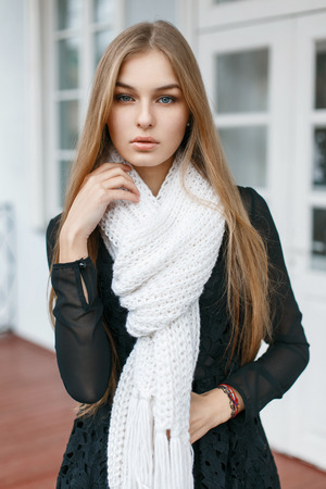Fashionable stylish girl with a white scarf is a warm on the background of retro building Stock Photo