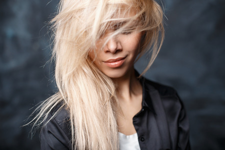 tousled: Close-up portrait of a beautiful woman with tousled blond hair and beautiful lips in a stylish black shirt Stock Photo