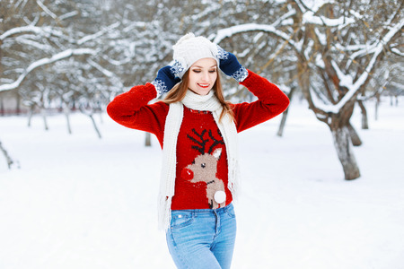 female christmas: Pretty Woman in red knitted sweater with a deer standing in a winter park.