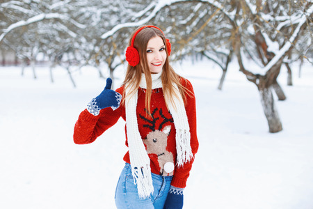 muff: Young beautiful girl in a red sweater with a reindeer and winter headphones to have fun in the park. Showing thumbs up sign of quality
