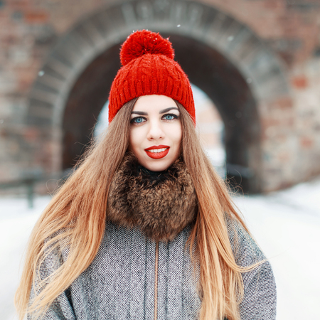 rock wool: Young beautiful woman in a red hat and coat with fur on a winter day