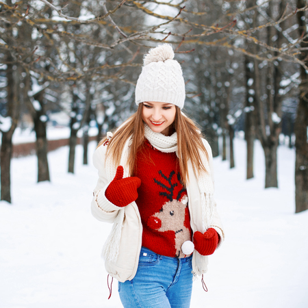 knit cap: Lovely girl with a stylish retro sweater, a white winter jacket and knit cap looking down on the background of the park Stock Photo