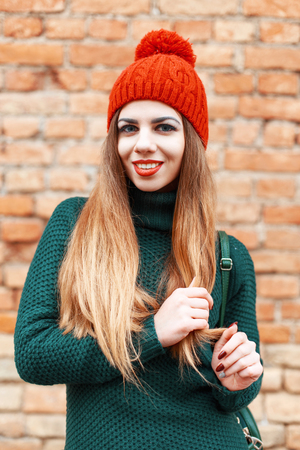 knitted jacket: Beautiful cute girl in a red cap and green knitted jacket standing near red brick wall Stock Photo