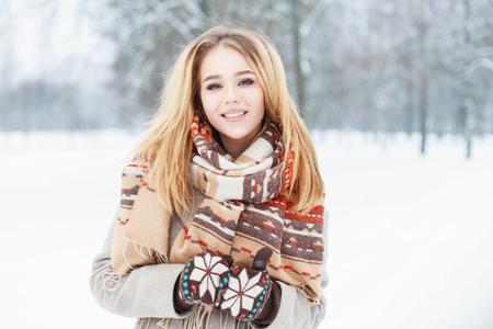 Mladá krásná dívka s roztomilou úsměvem ve vrcholném šálu a rukavice v zimní den