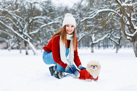 Beautiful girl in red knitted sweater walking a dog on a white snowy background. Banco de Imagens