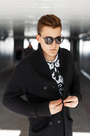 black sweater: stylish young man in black sweater and sunglasses on a sunny day Stock Photo