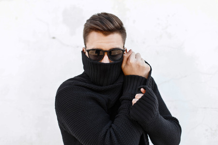 Young fashionable guy in black sunglasses vite and covers the face with a cloth.