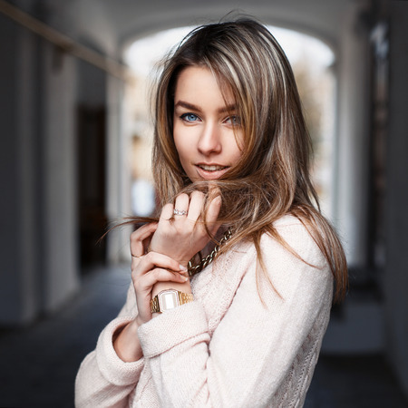 Outdoors Portrait of a young beautiful woman in fashionable clothes
