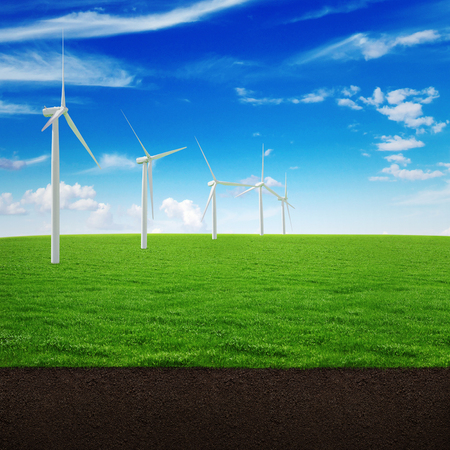 Windmill green energy on a beautiful landscape of green grass, the soil and the sky with clouds Banco de Imagens