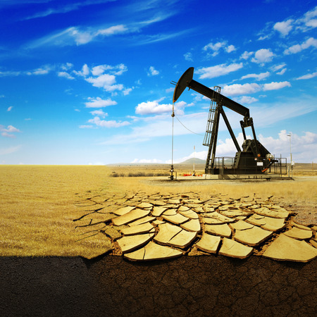 Oil pump oil rig energy industrial machine for petroleum on the background of dry earth with cracks. Concept Ecology