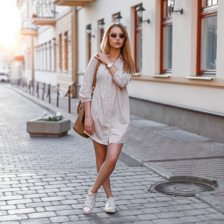 Beautiful young fashion girl in sunglasses, handbags and sneakers standing on a sunset background Standard-Bild