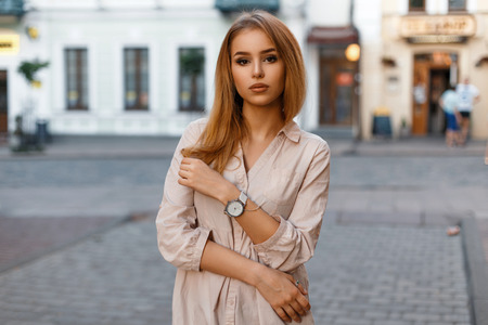 Stylish beautiful woman posing on a background of a building