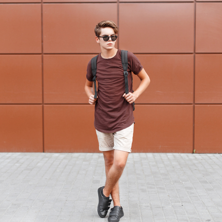 Young handsome man in summer clothes is posing near the wall