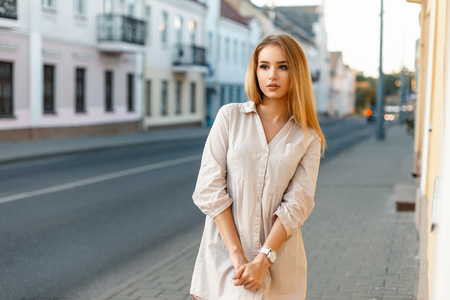 Beautiful woman in shirt standing near the road on the background buildings. Stockfoto