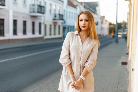 Mujer hermosa en la camisa de pie cerca de la carretera en los edificios del fondo. Foto de archivo