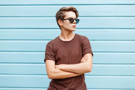 Young stylish handsome man is posing next to a bright blue wall.