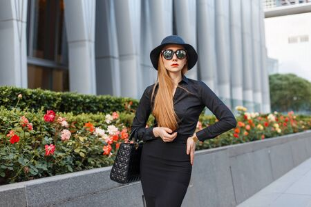black hat: Stylish young girl in a hat and black clothing with sunglasses against a background of a modern building.