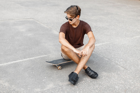 sits: Young handsome man with hairstyle in sunglasses sits on a skateboard. Stock Photo