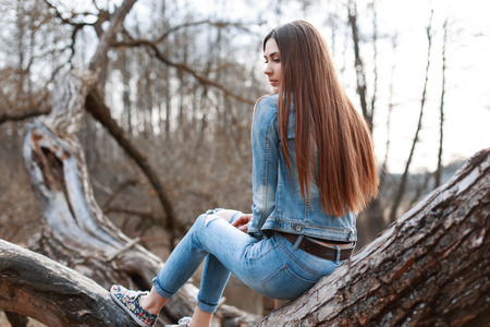 mezclilla: Niña hermosa en la chaqueta de mezclilla y pantalones vaqueros se sienta en un árbol y sueños.