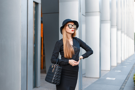 strict: Successful stylish young girl in a strict fashion clothes with a hat. Stock Photo