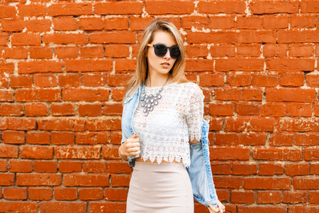 women subtle: Beautiful girl in vintage lace blouse and sunglasses removes his jacket. Stock Photo
