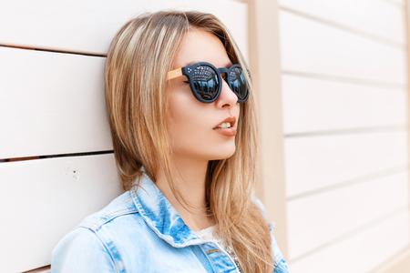 chaqueta: Retrato de primer plano de una hermosa joven en gafas de sol y una chaqueta de mezclilla en la playa cerca de la pared de madera